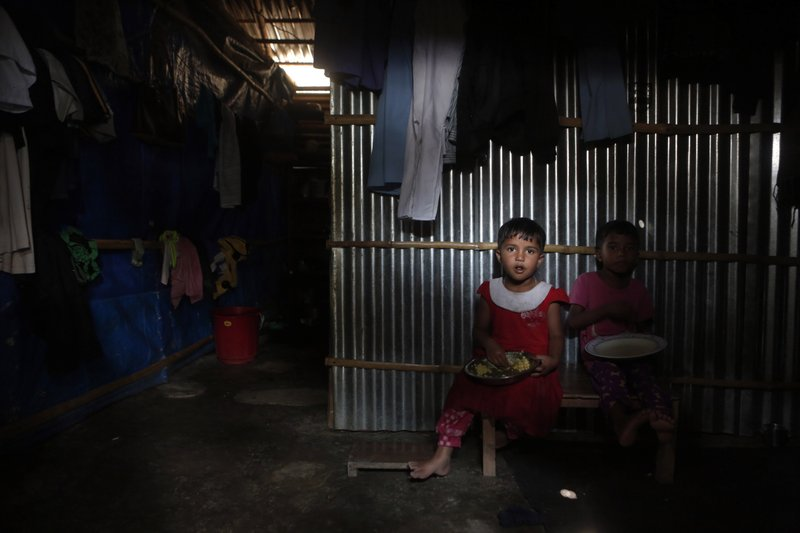 In this Sunday, Sept. 10, 2017, photo, Rohingya children have their lunch inside a temporary shelter in a camp in Kathmandu, Nepal. Recent violence in Myanmar has driven hundreds of thousands of Rohingya Muslims to seek refuge across the border in Bangladesh. Only about 250 Rohingya live in Nepal since anti-Muslim riots erupted in Myanmar in 2012, according to the U.N. refugee agency, which offers them education and medical support. The refugees live in a ramshackle camp carved out on a slope on the outskirts of the capital, Kathmandu. Their huts of tin, bamboo and plastic sheets are connected by narrow stone steps.
