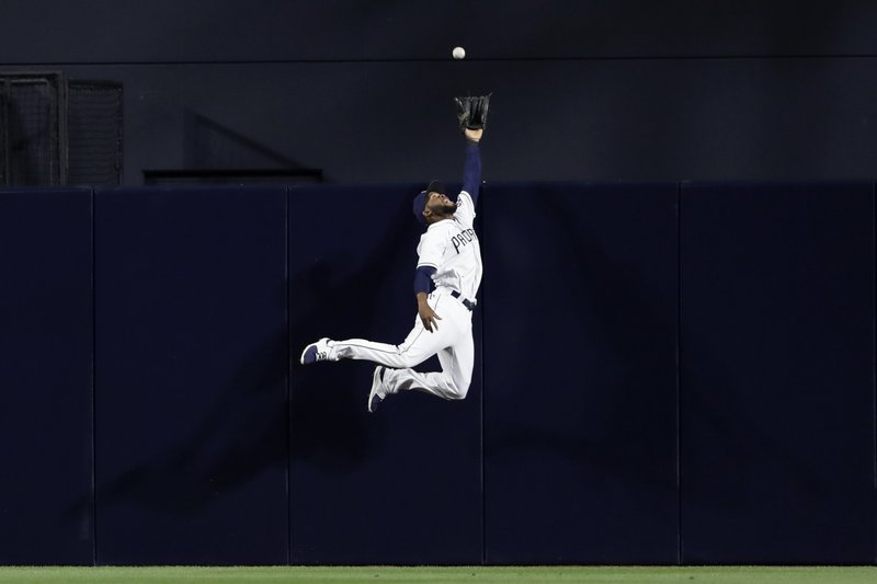 San Diego Padres center fielder Manuel Margot leaps but misses a home run hit by the Milwaukee Brewers' Jesus Aguilar during the sixth inning of a baseball game, Monday, May 15, 2017, in San Diego. (AP Photo/Gregory Bull)