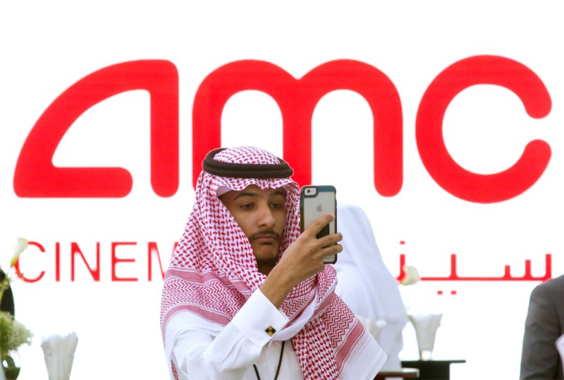 First saudi cinema opens with popcorn and black panther a visitor takes a selfie with a screen displaying the announcement of the first cinema at the king abdullah financial district theater in riyadh malvernweather Choice Image