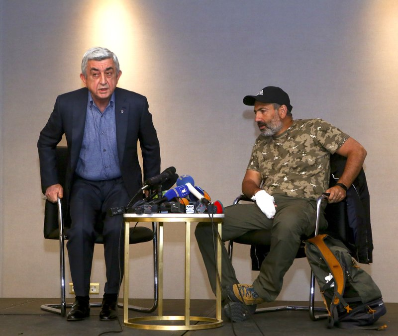 In this photo taken on Sunday, April 22, 2018, former Armenian President Serzh Sargsyan, left, leaves a meeting with protest leader Nikol Pashinian, right, in Yerevan, Armenia. Armenian Prime Minister Serzh Sargsyan has resigned, according to his website.