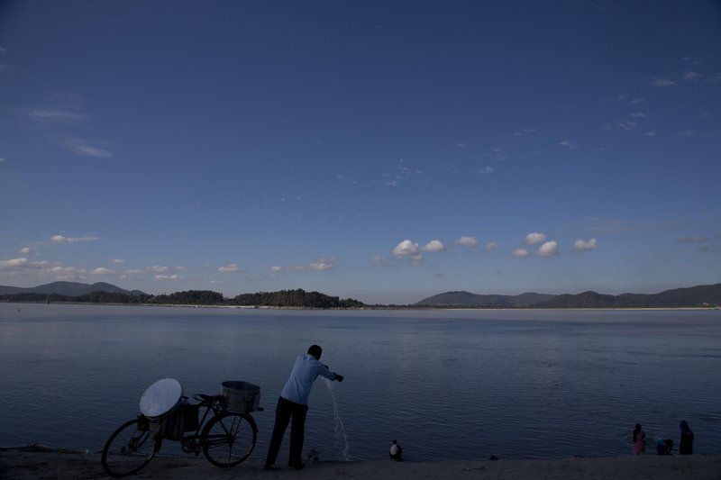 In this Monday, Dec.11, 2017 photo, an Indian fish seller cleans his drum at the river Brahmaputra in Gauhati, India. Officials in India's northeast are complaining that Chinese construction activity on the upper reaches of one of the largest rivers that flows into India are likely turning the waters downstream turbid and unfit for human consumption.