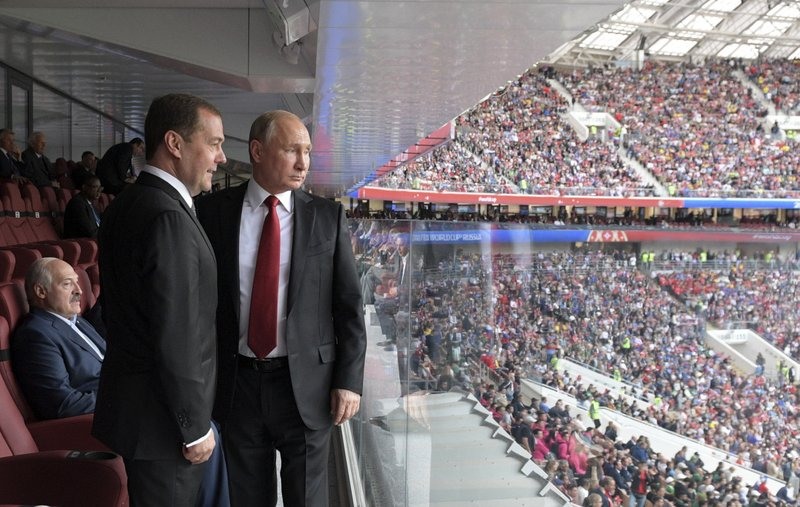 Russian President Vladimir Putin, right, and Russian Prime Minister Dmitry Medvedev look at the field during the match between Russia and Saudi Arabia which opens the 2018 soccer World Cup, at the Luzhniki stadium in Moscow, Russia, Thursday, June 14, 2018. Belarusian President Alexander Lukashenko, is seen behind them on the left.
