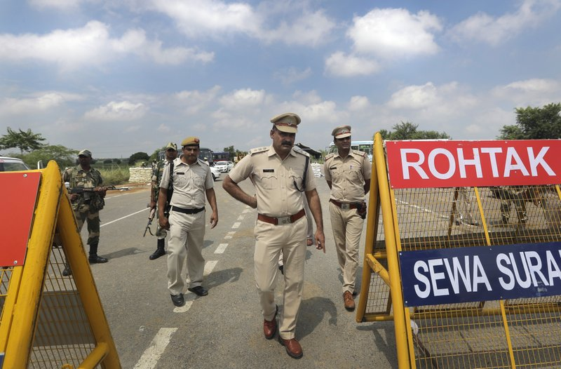 Indian policemen stand guard at a temporary road blockade near Sunaria Jail where Dera Sacha Sauda sect chief Gurmeet Ram Rahim Singh is being held in Rohtak, about 80 kilometers (50 miles) from New Delhi, India, Monday, August 28, 2017. A curfew is in place in a north Indian town where a spiritual guru who was convicted of rape last week is scheduled to be sentenced on Monday. A judge will travel to the prison where the guru has been held since being convicted Friday. The conviction sparked deadly protests.