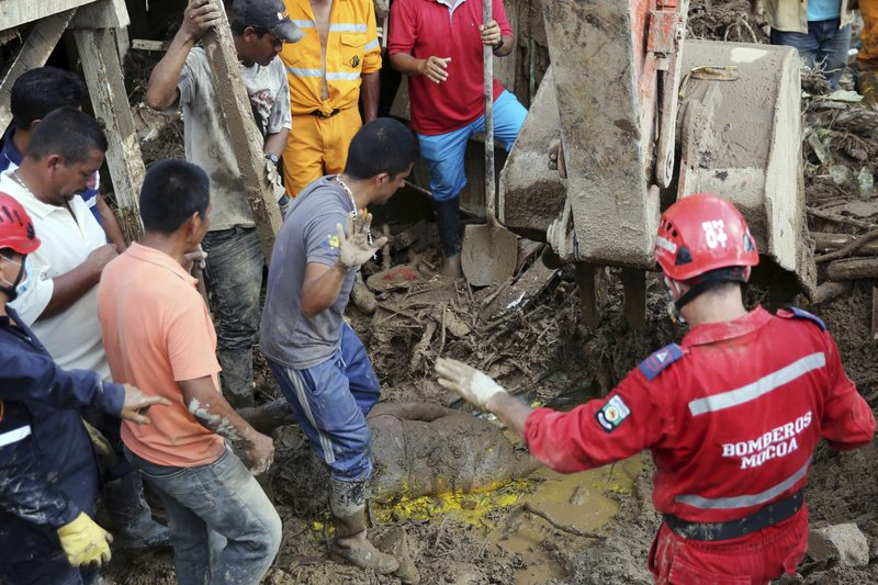 "Firefighters and neighbors stop their work as they found the body of a woman in Mocoa, Colombia, Sunday, April 2, 2017. Colombia's President Juan Manuel Santos, who has declared Mocoa a disaster area, said that at least 207 were killed but that the death toll was changing ""every moment."" Authorities said another 200 people, many of them children, were injured and just as many were unaccounted for amid the destruction."