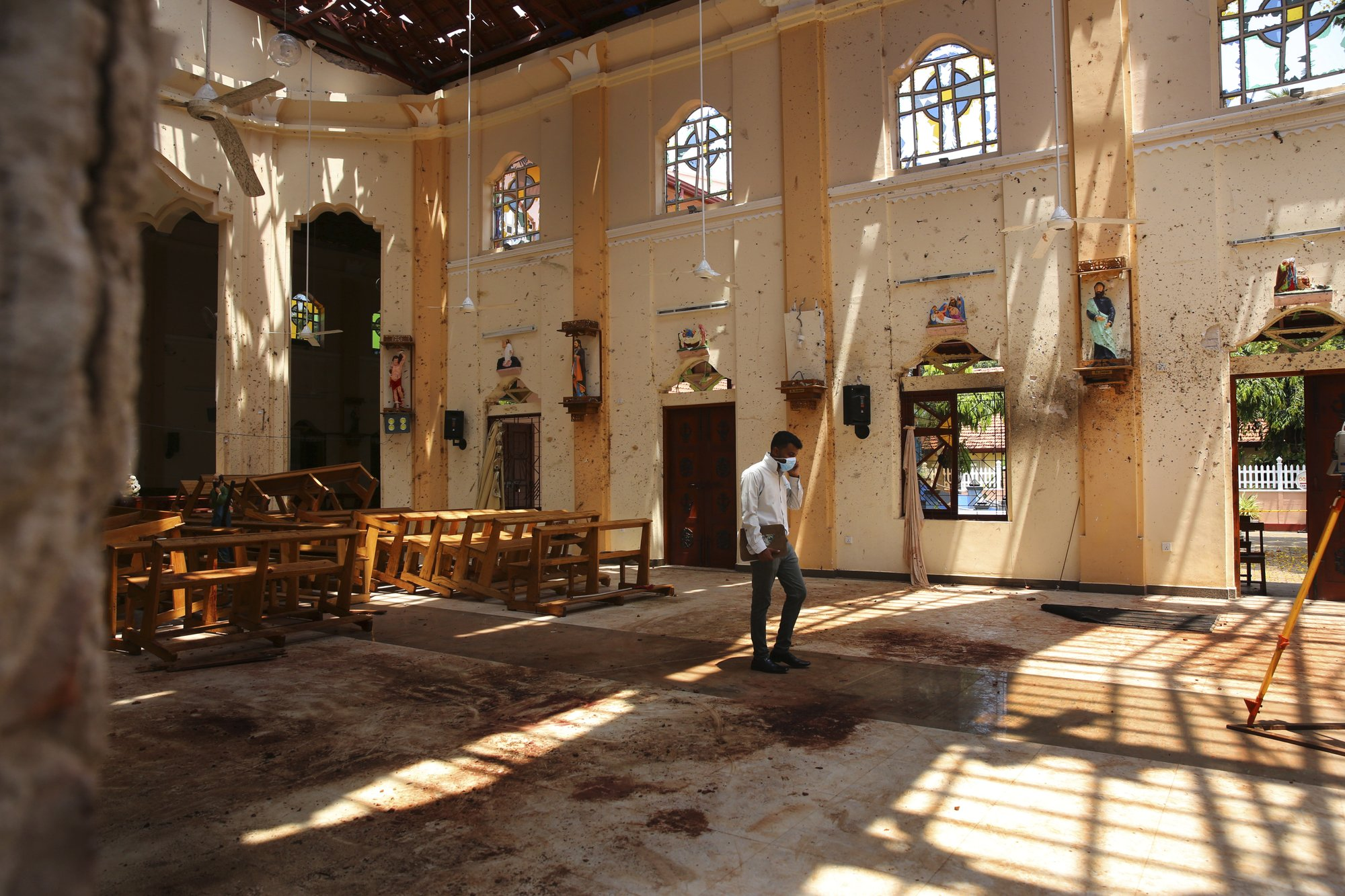 In this Thursday, April 25, 2019 photo, a surveyor walks inside the damaged St. Sebastian's Church where a suicide bomber blew himself up on Sunday Easter in Negombo, north of Colombo, Sri Lanka. Nearly a week later, even after the cleaners have come through, the blood can still be seen clearly. The statues of Jesus and the saints are still speckled with fragments of shrapnel. The smell of death is everywhere, though the bodies are long gone. (AP Photo/Manish Swarup)