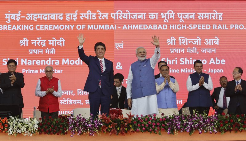 Japanese Prime Minister Shinzo Abe, left and Indian Prime Minister Narendra Modi wave during the ground breaking ceremony for high speed rail project in Ahmadabad, India, Thursday, Sept. 14, 2017.