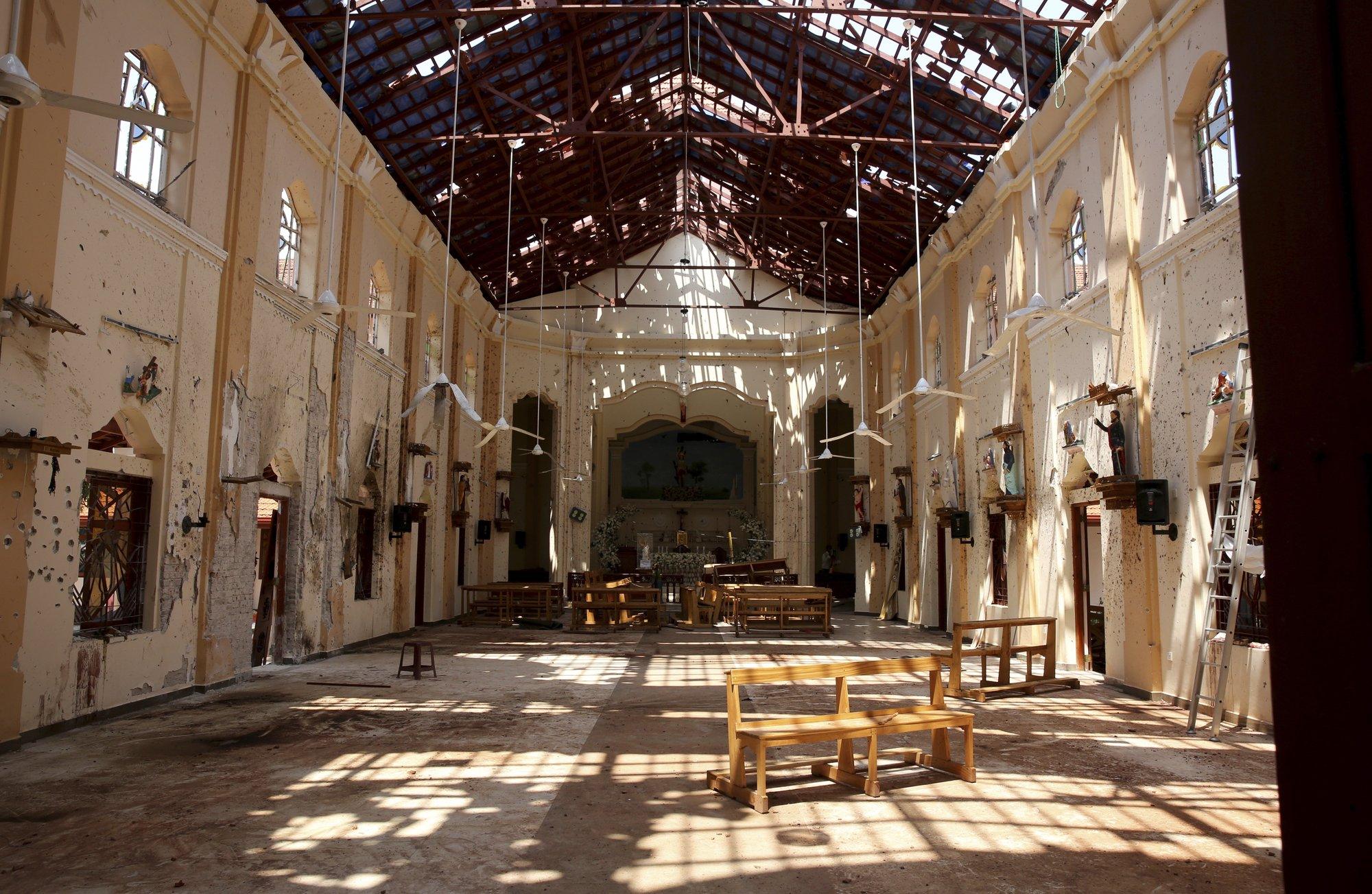 In this Thursday, April 25, 2019 photo, sunlight steams in from gaping holes at St. Sebastian's Church in Negombo, north of Colombo, Sri Lanka. Nearly a week later, the smell of death is everywhere, though the bodies are long gone. Yet somehow, there's a beauty to St. Sebastian's, a neighborhood church in a Catholic enclave north of Sri Lanka's capital, where a man calmly walked in during Easter services with a heavy backpack and blew himself up. (AP Photo/Manish Swarup)