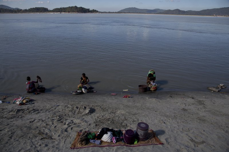 In this Monday, Dec.11, 2017 photo, Indian women wash their clothes in the river Brahmaputra in Gauhati, India. Officials in India's northeast are complaining that Chinese construction activity on the upper reaches of one of the largest rivers that flows into India are likely turning the waters downstream turbid and unfit for human consumption.