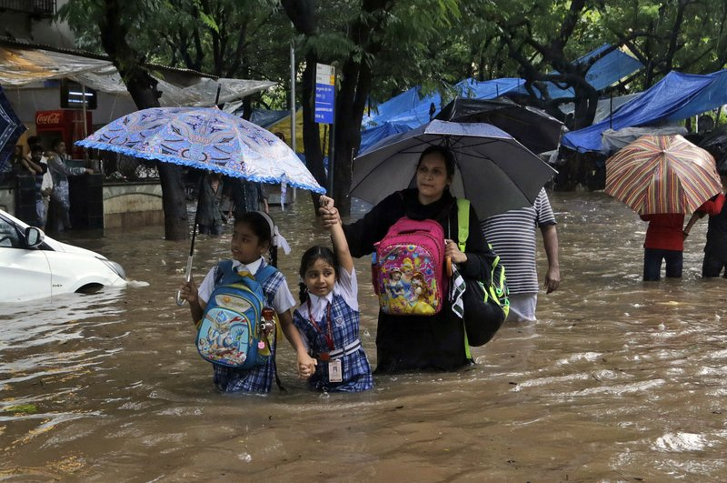 In this Tuesday, Aug. 29, 2017 file photo, schoolchildren wade past a waterlogged railway street in the rain in Mumbai, India. Two massive, rain-soaked cities on opposite sides of the world are struggling with swirling, brackish waters that have brought death and devastation. For Houston, it's unprecedented. For Mumbai, it's painfully common. India's financial capital was especially hard hit, with water swamping offices, schools and roads and about 60 people killed, 33 alone in Thursday's collapse of a 117-year-old apartment building whose foundation had been weakened by the flooding.