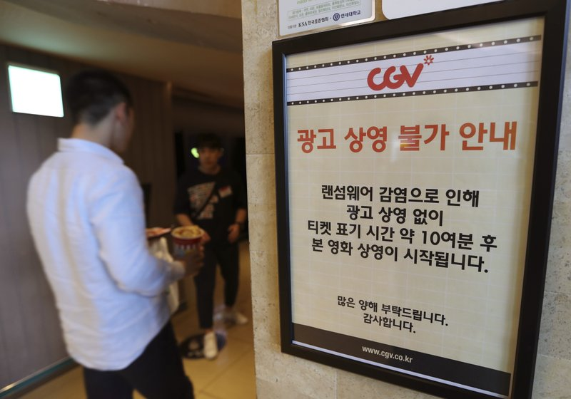 "A customer walks by the notice about ""ransomware"" at CGV theater in Seoul, South Korea, Monday, May 15, 2017. The letters read ""Due to ransomware affection, we are unable to screen advertisement. The movie is going to start 10 minutes after the ticket time."""