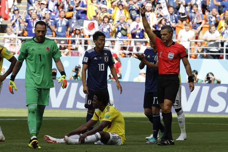 Referee Damir Skomina from Slovenia shows the red card to Colombia's Carlos Sanchez, bottom, during the group H match between Colombia and Japan at the 2018 soccer World Cup in the Mordavia Arena in Saransk, Russia, Tuesday, June 19, 2018.