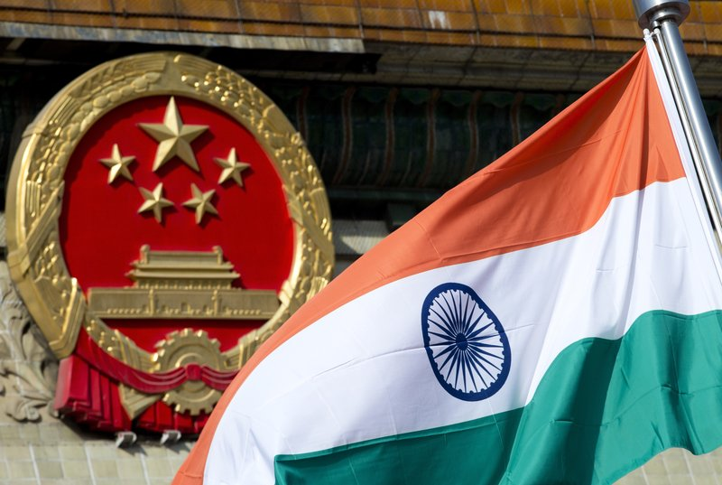 In this Wednesday, Oct. 23,2013, file photo, an Indian national flag is flown next to the Chinese national emblem during a welcome ceremony for visiting Indian officials outside the Great Hall of the People in Beijing. India says it is ready to hold talks with China with both sides pulling back their forces to end a standoff along a disputed territory high in the Himalayan mountains.