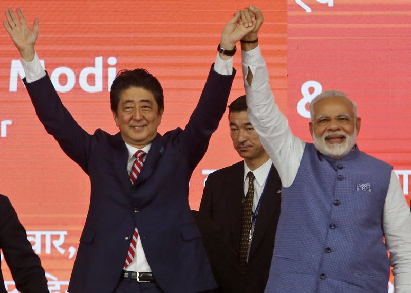 Japanese Prime Minister Shinzo Abe, left and Indian Prime Minister Narendra Modi hold hands during the ground breaking ceremony for high speed rail project in Ahmadabad, India, Thursday, Sept. 14, 2017.