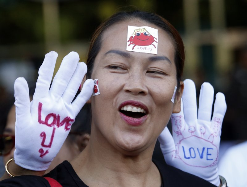 "In this Wednesday, Sept. 27, 2017, file photo, supporters of Thai former Prime Minister Yingluck Shinawatra display messages on their hands reading ""Love Pu,"" which is Yingluck's Thai nickname, outside the Supreme Court in Bangkok, Thailand."
