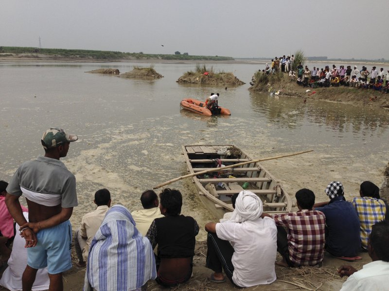 Rescuers search in the Yamuna River as villagers gather after a country boat, seen in foreground, capsized near Baghpat town in Uttar Pradesh state, India, Thursday, Sept.14, 2017. The boat crowded with construction workers capsized early Thursday and nineteen bodies have been pulled out of the river so far.