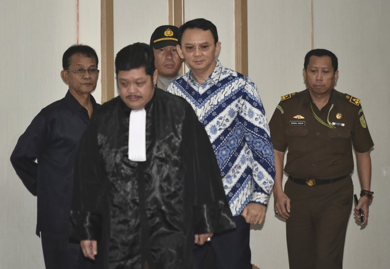 "Jakarta Governor Basuki ""Ahok"" Tjahaja Purnama, center, is escorted by prosecutors as enters the court room for his sentencing hearing in Jakarta, Indonesia, Tuesday, May 9, 2017. The minority Christian governor is currently on trial on accusation of blasphemy following his remark about a passage in the Quran that could be interpreted as prohibiting Muslims from accepting non-Muslims as leaders."