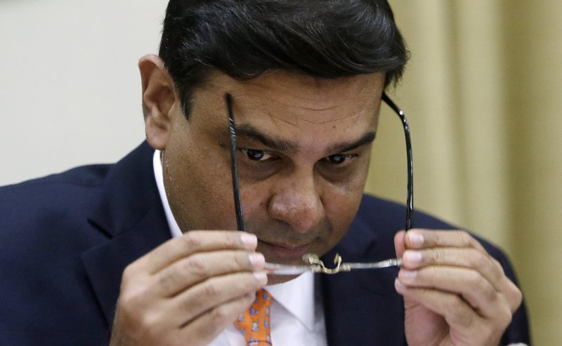 Reserve Bank of India Governor Urjit Patel, holds his spectacles during a press conference in Mumbai, India, Wednesday, Aug. 2, 2017. India's central bank Wednesday cuts its key interest rate by a quarter of a percentage point on Wednesday, raising hopes of lower borrowing costs for households as inflation ebbs.