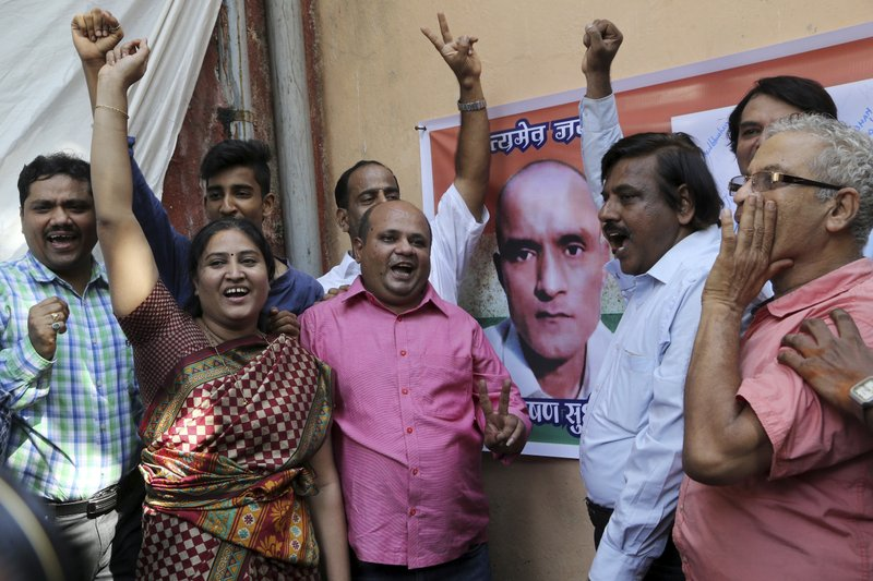 Friends of Indian naval officer Kulbhushan Jadhav celebrate the International Court of Justice order on Jadhav as they gather near a portrait of him in Mumbai, India, Thursday, May 18, 2017. The U.N. court on Thursday ordered Pakistan not to execute the Indian naval officer convicted of espionage and terrorism, in a case that has further strained relations between the Asian neighbors.