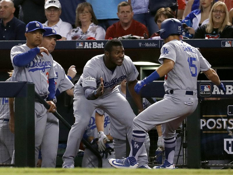 Los Angeles Dodgers  Austin Barnes (15) celebrates with Yasiel Puig in the  dugout after hitting a solo home run during the sixth inning of game 3 of  ... d303bbd09