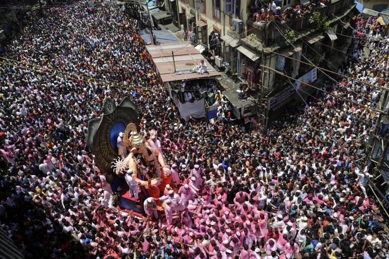 In this Tuesday, Sept. 5, 2017, file photo, Hindu devotees participate in a procession towards the Arabian Sea with a giant idol of the elephant-headed god Ganesha to immerse it on the final day of the ten-day long Ganesha Chaturthi festival in Mumbai, India.