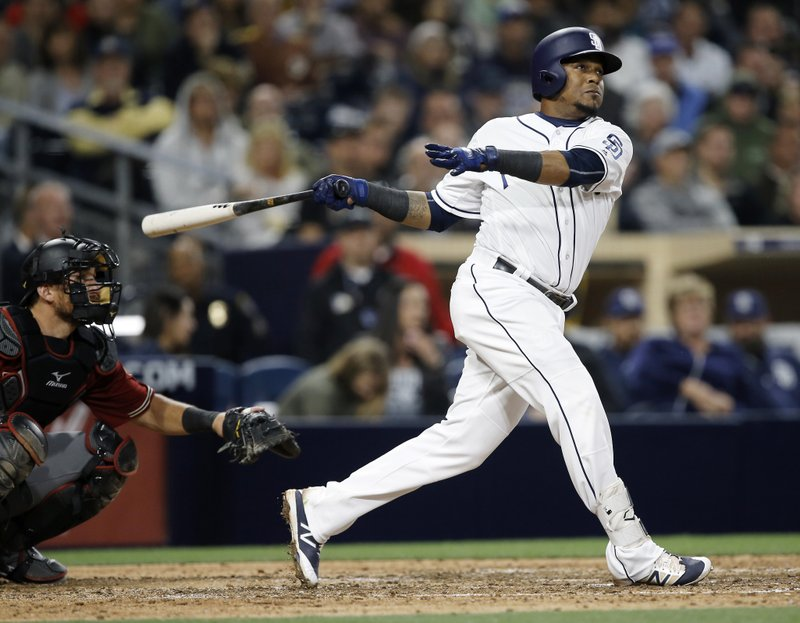 San Diego Padres' Erick Aybar follows through on a solo home run with Arizona Diamondbacks catcher Jeff Mathis watching during the eighth inning of a baseball game in San Diego, Wednesday, April 19, 2017. (AP Photo/Alex Gallardo)