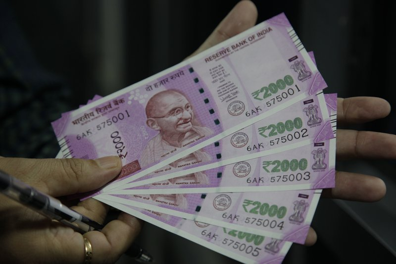 In this Nov. 13, 2016 file photo, an Indian holds 2000 rupee currency notes in Jammu, India. Police say at least one rat slipped through a hole in the back of an ATM in northeastern India and ate more than $19,000 in currency.