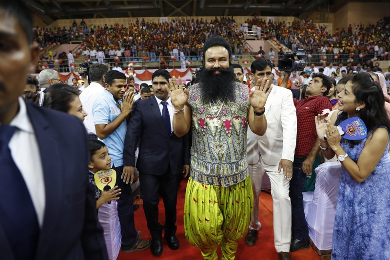 "In this Oct. 5, 2016 file photo, Indian spiritual guru who calls himself Saint Dr. Gurmeet Ram Rahim Singh Ji Insan, center, greets followers as he arrives for a press conference ahead of the release of his new movie ""MSG, The Warrior Lion Heart,"" in New Delhi, India. Several cities in north India were under a security lock down Thursday ahead of a verdict in a rape trial involving a controversial and hugely popular spiritual leader."