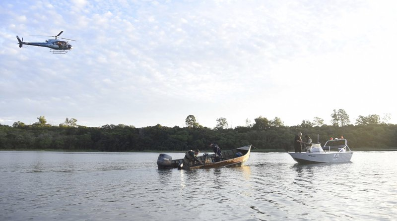 "Police inspect a boat that assailants used to escape after a massive armored car company robbery, in the Parana River, border with Brazil and Paraguay, Monday, April 24, 2017. A gang of over 50 armed bandits stole several million dollars from a vault in Paraguay, in what local officials are dubbing the ""robbery of the century"". The culprits, who police said were from Brazil, killed one police officer during the Monday raid."