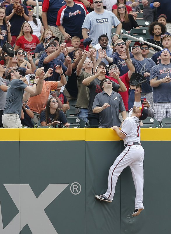 Atlanta Braves' center fielder Ender Inciarte (11) goes up the wall as fans reach for a ball ht for a home run by San Diego Padres' Ryan Schimpf in the second inning of a baseball game Sunday, April 16, 2017, in Atlanta. (AP Photo/John Bazemore)