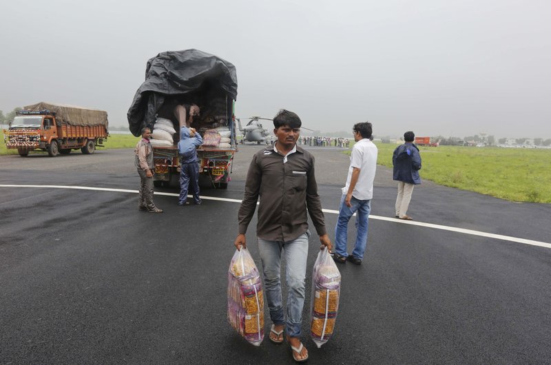 An Indian man carries relief materials prior to loading them in to an air force helicopter at an airport in Deesa, Gujarat, India, Wednesday, July 26, 2017. At least 29 people have died in the state of Gujarat amid torrential rains. This week's deaths have taken the toll the state to 83 since the start of the monsoon season which runs from June through September.