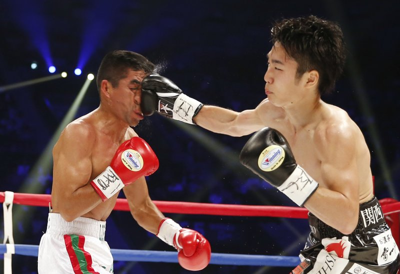 In this Saturday, May 20, 2017, photo, Japan's Shiro Ken, right, lands a right on the face of Mexican champion Ganigan Lopez in the third round of their WBC light flyweight boxing world title match in Tokyo, Saturday, May 20, 2017. Ken won the title by a 2-0 decision.