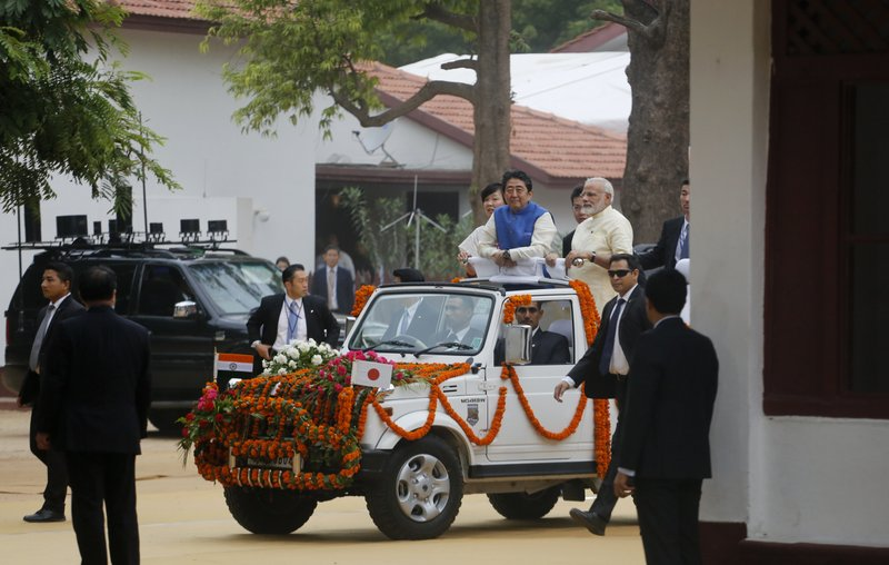 Japanese Prime Minister Shinzo Abe, center, flanked by his wife Akie Abe, and Indian Prime Minister Narendra Modi arrive in an open vehicle at Sabarmati Ashram, or Gandhi Ashram, in Ahmadabad, India, Wednesday, Sept. 13, 2017. Abe is on a two-day official visit to India.