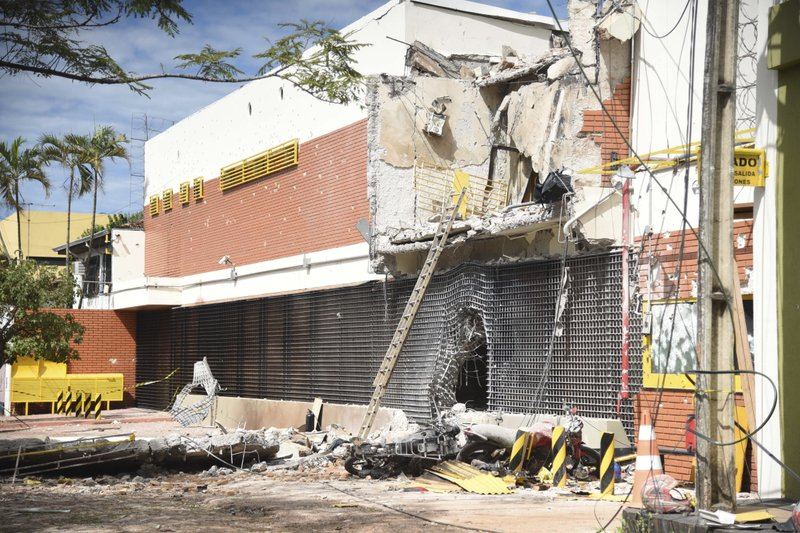 "The partly demolished building of the armored car company Prosegur is seen after assailants blew it up, in Ciudad del Este, Paraguay, Monday, April 24, 2017. A gang of over 50 armed bandits stole several million dollars from a vault in the company, in what local officials are dubbing the ""robbery of the century"". The culprits, who police said were from Brazil, killed one police officer during the Monday raid."