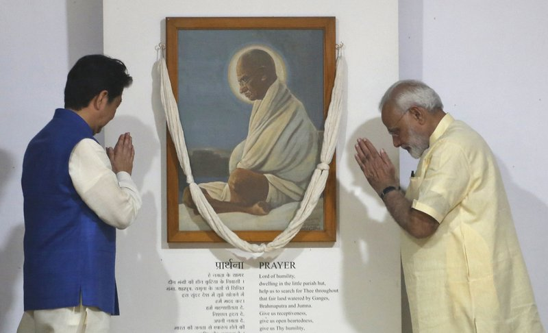 Japanese Prime Minister Shinzo Abe, left, and Indian Prime Minister Narendra Modi pay their respects in front of a portrait of Mahatma Gandhi at Sabarmati Ashram, or Gandhi Ashram, in Ahmadabad, India, Wednesday, Sept. 13, 2017. Abe is on a two-day official visit to India.