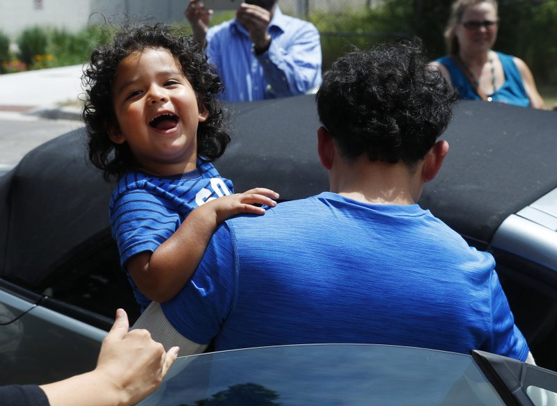 reunited immigrant children scooped up into parents arms
