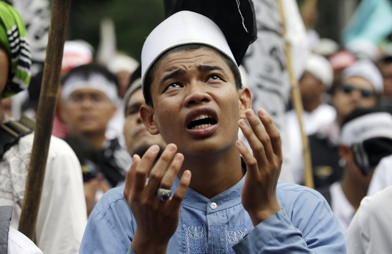 "Muslim protesters pray during a protest against Jakarta's Christian Governor Basuki ""Ahok"" Tjahaja Purnama outside a court where his trial is held in Jakarta, Indonesia, Tuesday, May 9, 2017. An Indonesian court on Tuesday sentenced the minority Christian governor of Jakarta to two years in prison for blaspheming the Quran, a shock decision that undermines the country's reputation for practicing a moderate form of Islam."