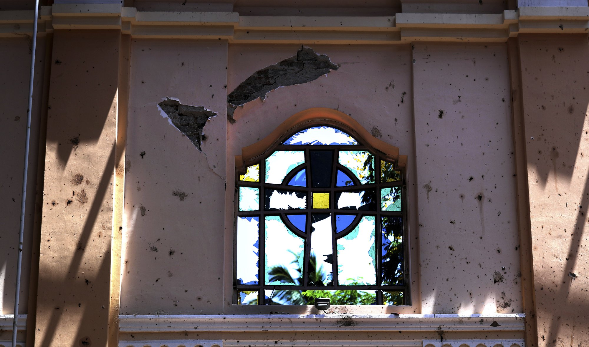 In this Thursday, April 25, 2019 photo, a stained-glass window stands broken at Sebastian's Church, where a suicide bomber blew himself up on Easter Sunday in Negombo, north of Colombo, Sri Lanka. Nearly a week later, the smell of death is everywhere, though the bodies are long gone. Yet somehow, there's a beauty to St. Sebastian's, a neighborhood church in a Catholic enclave north of Sri Lanka's capital. You can see the beauty in the broken stained-glass windows. It's there as the sun shines through the roof's gaping holes. It's there in the little statues that refused to fall over, and despite the swarms of police and soldiers who seem to be everywhere now in the streets of the seaside town of Negombo. (AP Photo/Manish Swarup)