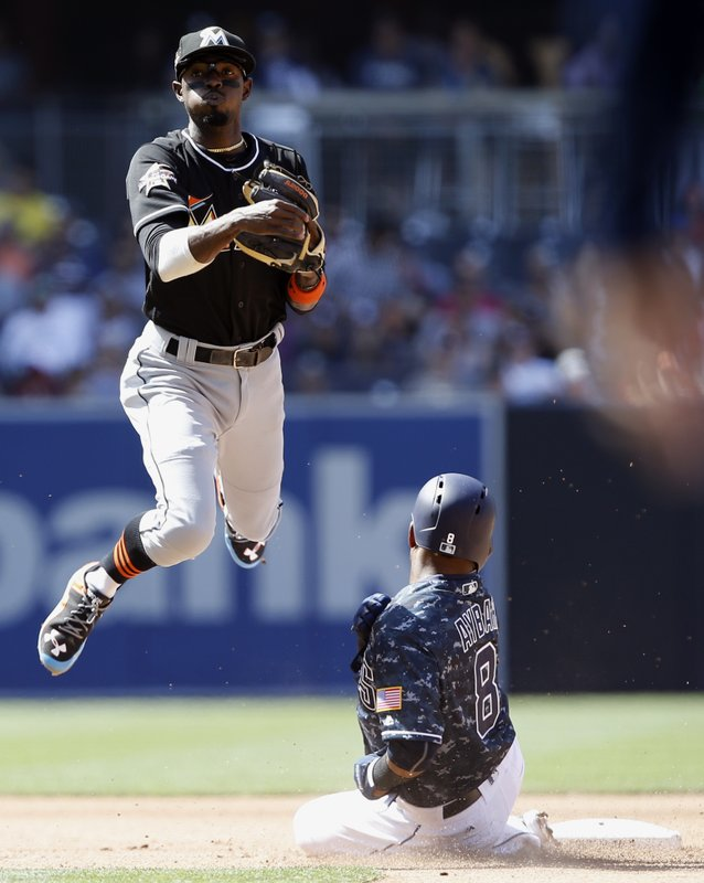 Miami Marlins second baseman Dee Gordon, left, leaps away from the forced out San Diego Padres' Erick Aybar (8), then throws to first to get Wil Myers for a double play during the fifth inning of a baseball game in San Diego, Sunday, April 23, 2017. (AP Photo/Alex Gallardo)