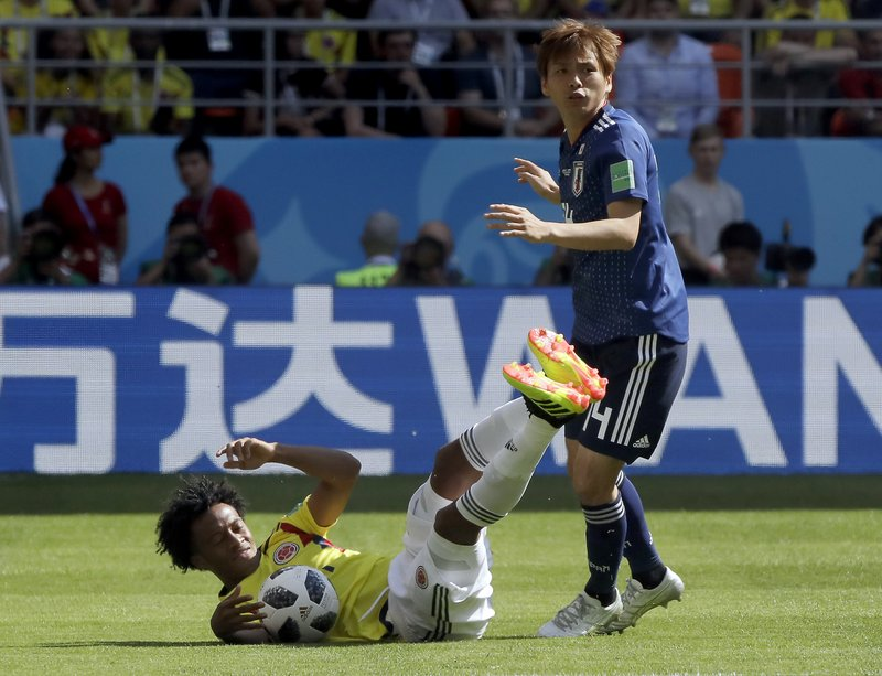 Colombia's Juan Cuadrado, left, andJapan's Takashi Inui, right, challenge for the ball during the group H match between Colombia and Japan at the 2018 soccer World Cup in the Mordavia Arena in Saransk, Russia, Tuesday, June 19, 2018.