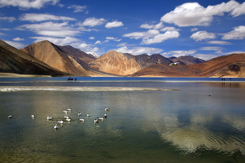 In this Sunday, June 17, 2016, photo, an Indian tourist rides on a horse back at the Pangong lake high up in Ladahak region of India. The Chinese soldiers hurled stones while attempting to enter Ladakh region near Pangong Lake on Tuesday but were confronted by Indian soldiers, said a top police officer. The officer said Indian soldiers retaliated but neither side used guns. There was immediately no comment from China.