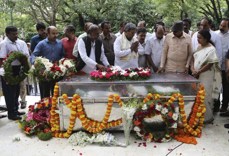 India's Karnataka state Chief Minister Siddaramaiah, center, pays his respects next to the casket of Indian journalist Gauri Lankesh during the public viewing of her body in Bangalore, India, Wednesday, Sept. 6, 2017. The Indian journalist was gunned down outside her home the southern city of Bangalore — the latest in a string of deadly attacks targeting journalists or outspoken critics of religious superstition and extreme Hindu politics.