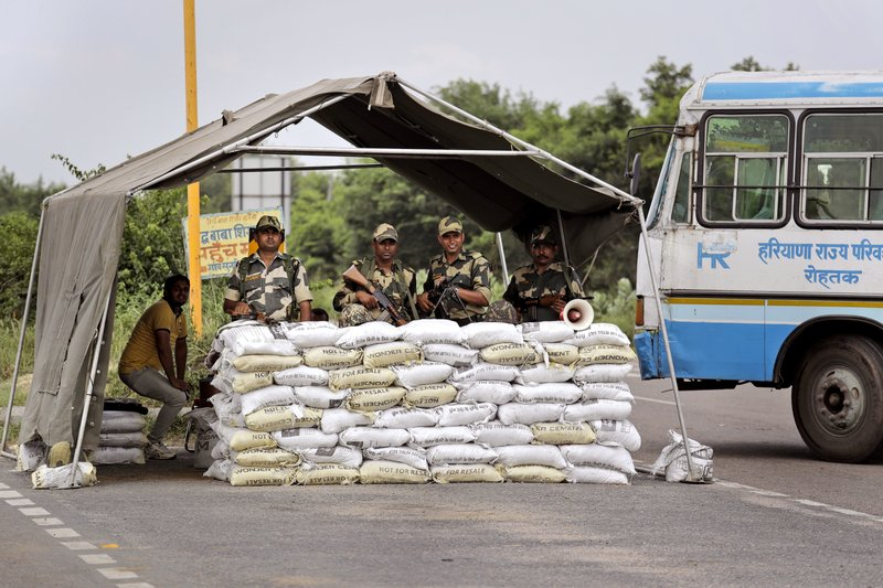 Indian Para-military force soldiers stand guard near Sunaria Jail where Dera Sacha Sauda sect chief Gurmeet Ram Rahim Singh is lodged in Rohtak, some 80 kilometers (50 miles) from New Delhi, India, Monday, Aug. 28, 2017. A curfew is in place in a north Indian town where a spiritual guru who was convicted of rape last week is scheduled to be sentenced on Monday. A judge will travel to the prison where the bling-loving guru has been held since being convicted Friday. The conviction sparked deadly protests.