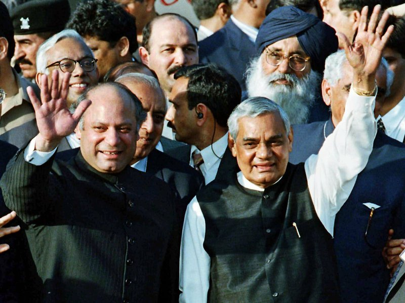 In this Feb. 20, 1999, file photo, Pakistani Prime Minister Nawaz Sharif, left, and his Indian counterpart Atal Bihari Vajpayee wave upon Vajpayee's arrival in Wagha border, 28 kilometers (17 miles) from Lahore, Pakistan. Vajpayee rode a bus to the Pakistani city of Lahore to meet with Pakistan counterpart, Nawaz Sharif, and sign a major peace accord.