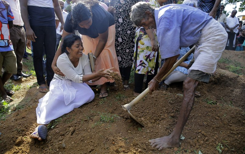 Wasanthi, a member of the Gomez family weeps over the gave of 9-year-old Bevon, who was killed in the Easter Sunday bombings in Colombo, Sri Lanka. (Credit: Eranga Jayawardena/AP.)