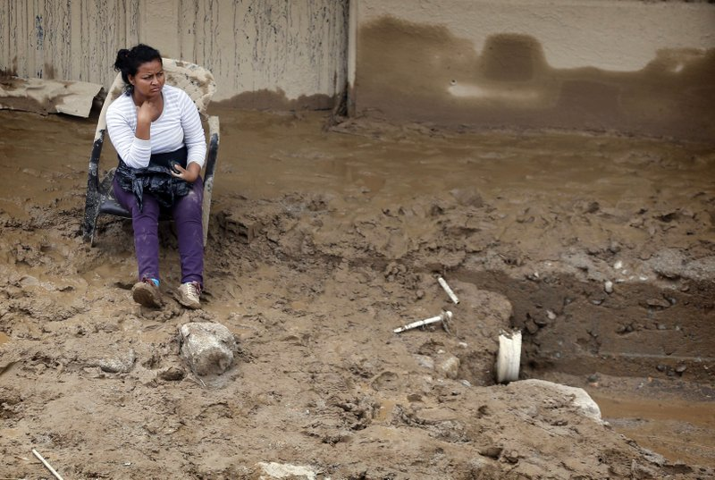 A woman sits on a chair in front of her house covered with mud in Mocoa, Colombia, Sunday, April 2, 2017. A grim search for the missing resumed at dawn Sunday in southern Colombia after surging rivers sent an avalanche of floodwaters, mud and debris through a city, killing at least 200 people and leaving many more injured and homeless.