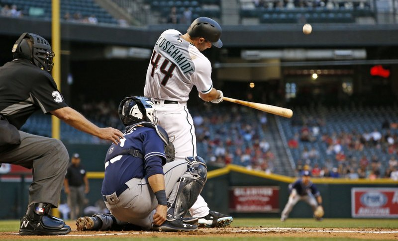Arizona Diamondbacks' Paul Goldschmidt connects for a home run as San Diego Padres' Austin Hedges, middle, and umpire Gary Cederstrom, left, look on during the first inning of a baseball game Tuesday, April 25, 2017, in Phoenix. (AP Photo/Ross D. Franklin)