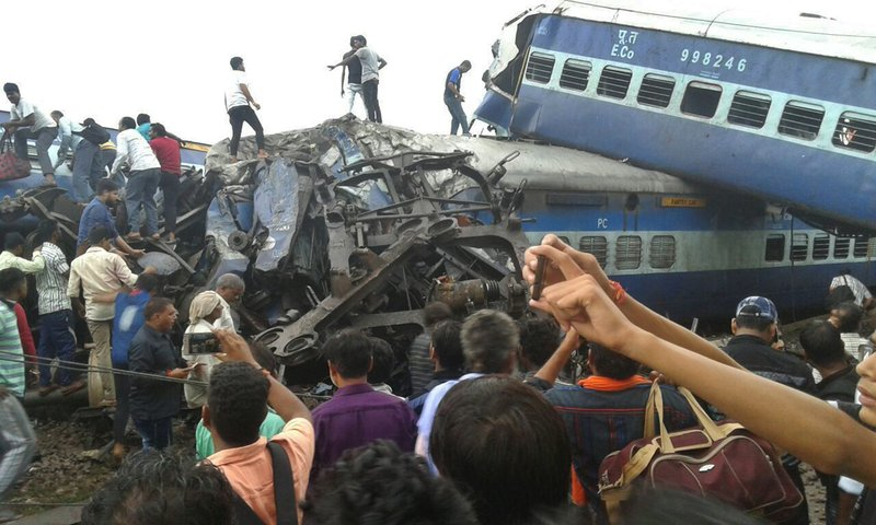 In this Saturday, Aug. 19, 2017, file photo, railway police and local volunteers look for survivors in the upturned coaches of the Kalinga-Utkal Express after an accident near Khatauli, in the northern Indian state of Uttar Pradesh. Six coaches of a passenger train derailed in northern India on Saturday.