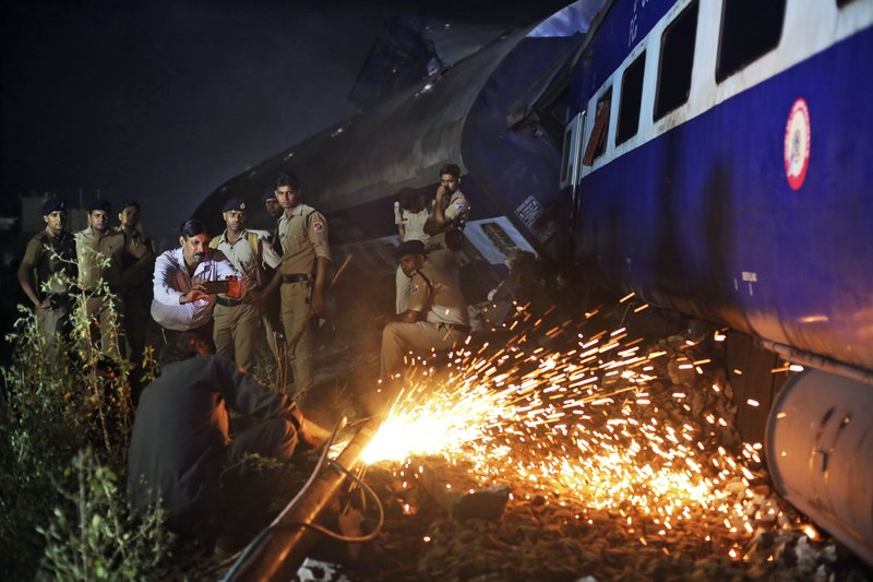 Indian police watch as rescue work is in progress near the upturned coaches of the Kalinga-Utkal Express after an accident near Khatauli, in the northern Indian state of Uttar Pradesh, India, Sunday, Aug. 20, 2017. Several coaches of the passenger train derailed, causing fatalities and injuries in northern India on Saturday, officials said.