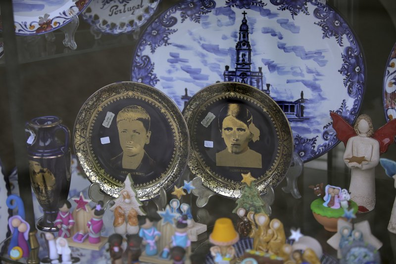 In this photo taken May 4, 2017, china plates with images of Francisco and Jacinta Marto are displayed for sale in a shop window in Fatima, Portugal. Pope Francis is visiting the Fatima shrine on May 12 and 13 to canonize Francisco and Jacinta Marto, two Portuguese shepherd children who say they saw visions of the Virgin Mary 100 years ago.