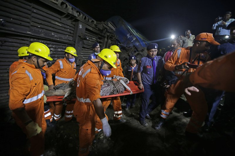 Rescuers carry the body of a victim recovered from upturned coaches of the Kalinga-Utkal Express after an accident near Khatauli, in the northern Indian state of Uttar Pradesh, India, Sunday, Aug. 20, 2017. Six coaches of a passenger train derailed in northern India on Saturday, killing more than 20 people and injuring dozens, officials said.